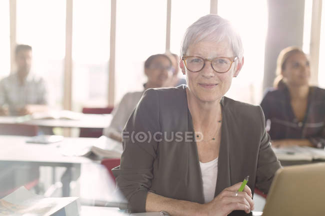 Portrait smiling senior woman at laptop in adult education classroom — Stock Photo