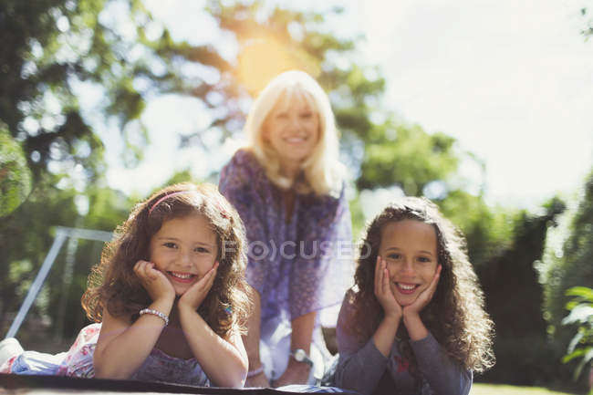 Portrait smiling grandmother with twin granddaughters in park — Stock Photo