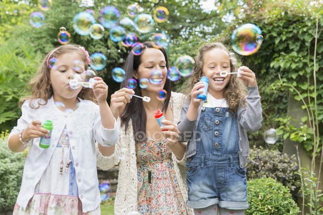 Mother and daughters blowing bubbles in backyard — Stock Photo