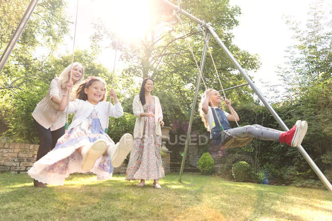 Carefree multi-generation women swinging in backyard — Stock Photo