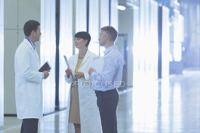 Scientists and businessman talking in factory corridor — Stock Photo
