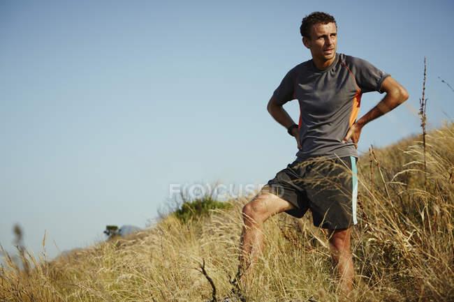 Tired runner taking a break on grassy trail — Stockfoto