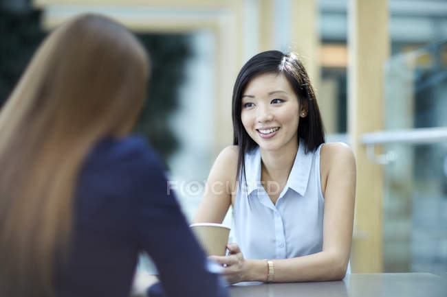 Smiling businesswomen talking on coffee break — Stock Photo