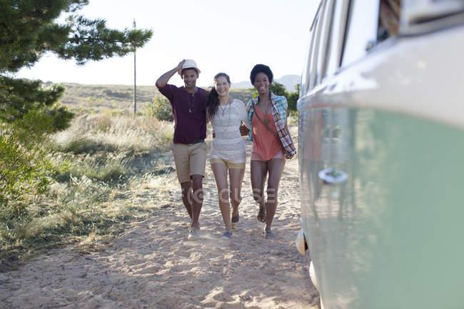 Friends walking to camper van on beach — Stock Photo