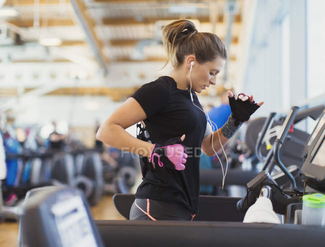 Woman running on treadmill at gym with headphones — Stock Photo