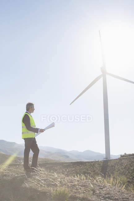 Businessman examining wind turbine in rural landscape — Stock Photo