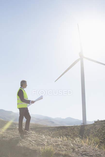 Businessman examining wind turbine in rural landscape — Stock Photo