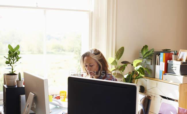 Окаменелая женщина, работающая в домашнем офисе — стоковое фото