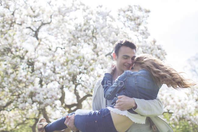 Людина підйому жінка під дерево з білим цвіте — стокове фото