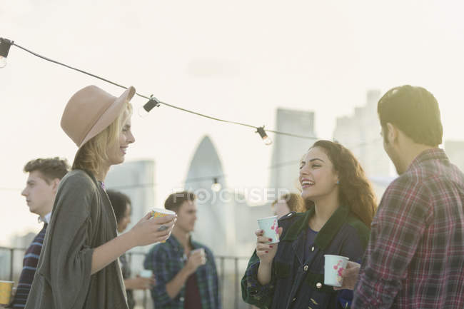 Young adult friends drinking and talking at rooftop party — Stockfoto