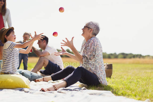 Grandmother and grandson juggling apples on picnic blanket in sunny field — Stock Photo