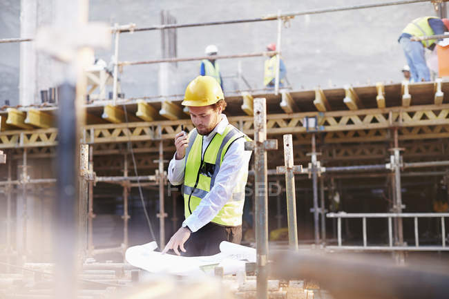 Engineer reviewing blueprints at construction site — Stock Photo