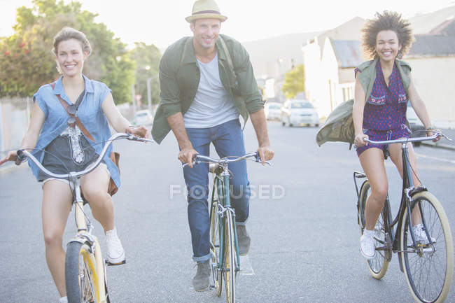Smiling friends riding bicycles on street — Stock Photo