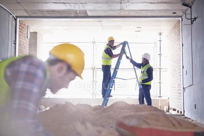 Працівник будівництва по сходах на будмайданчик — стокове фото