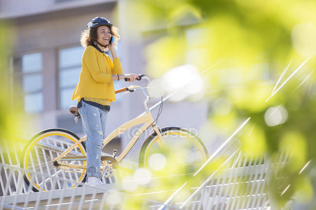 Smiling woman talking on cell phone on bicycle in city — Stock Photo