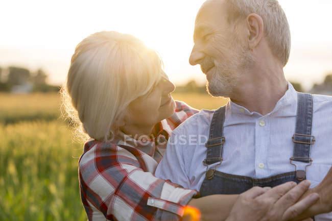 Закрыть ласковую пожилую пару, обнимающую сельскую местность — стоковое фото