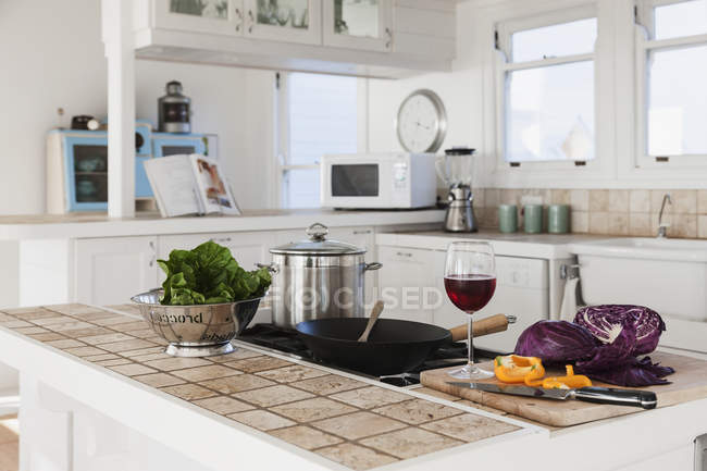 Vegetables and glass of red wine in kitchen — Stock Photo