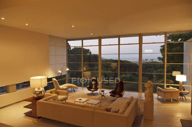 Modern living room overlooking trees and city in distance — Stock Photo