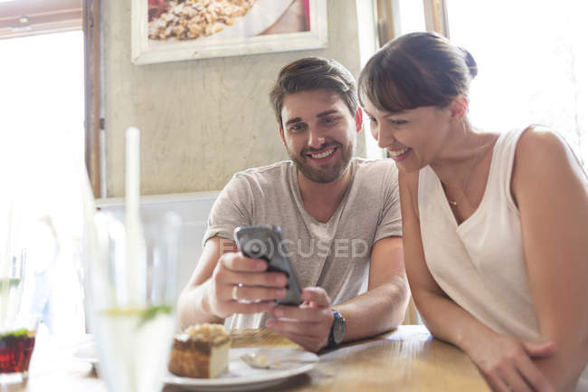 Couple texting with cell phone at cafe table — Stockfoto