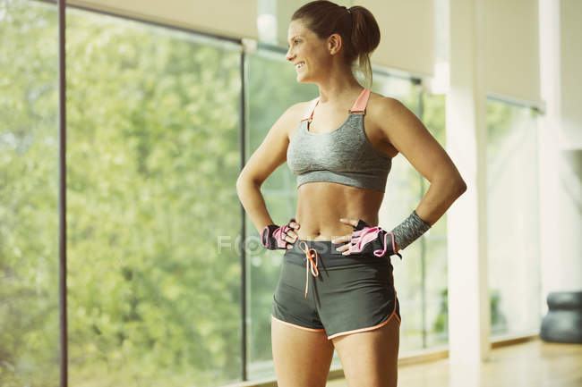 Smiling woman resting with hands on hips in gym studio — Stockfoto
