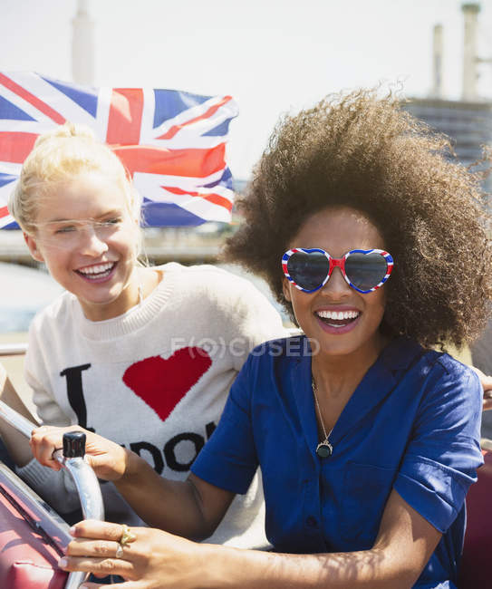 Portrait enthusiastic friends with British flag riding double-decker bus — Stock Photo