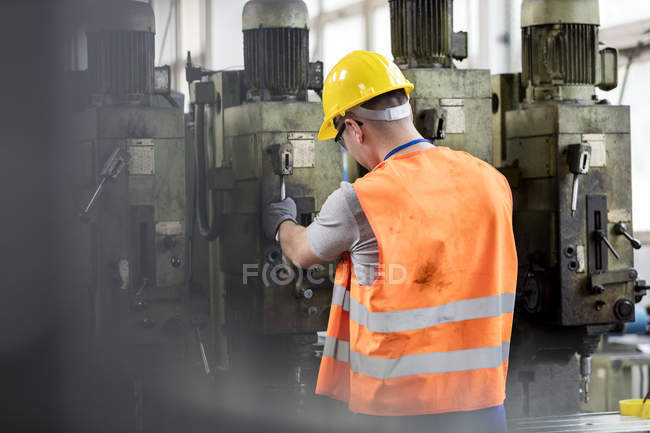 Worker in protective workwear operating machinery in factory — Stock Photo