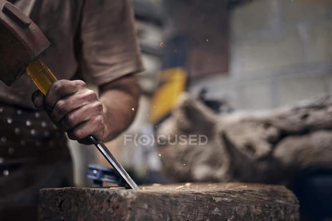 Blacksmith chiseling wood in workshop — Stock Photo