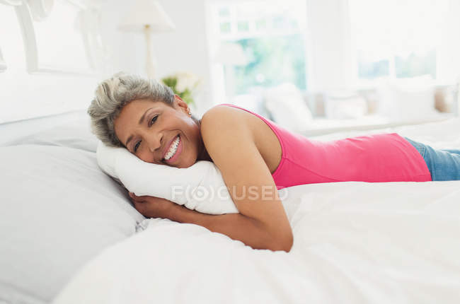 Portrait smiling mature woman laying on bed — Stockfoto