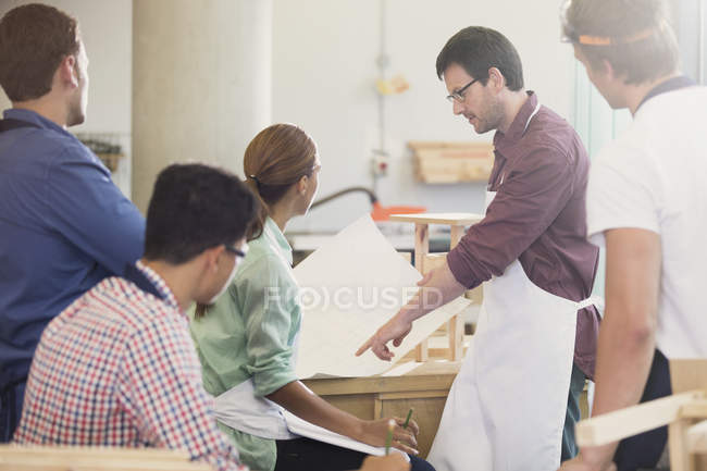 Carpentry teacher explaining blueprints to students in workshop — Stock Photo