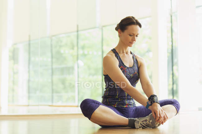Woman stretching in cobbler?s pose in gym studio — Stockfoto
