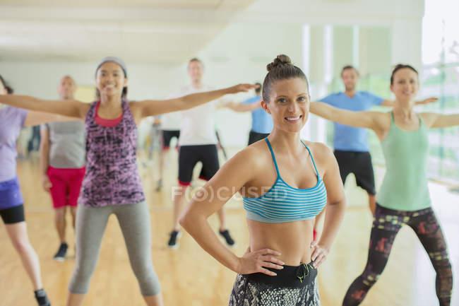 Portrait smiling fitness instructor leading aerobics class — Stock Photo