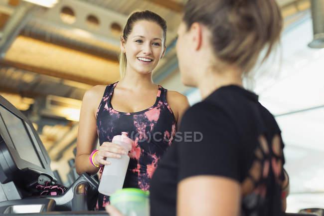 Lächelnde Frauen reden und Trinkwasser in Turnhalle — Stockfoto