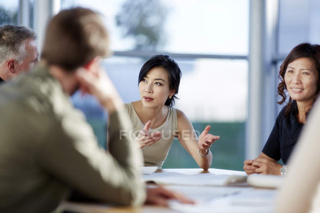 Successful adult business people talking in meeting — стоковое фото