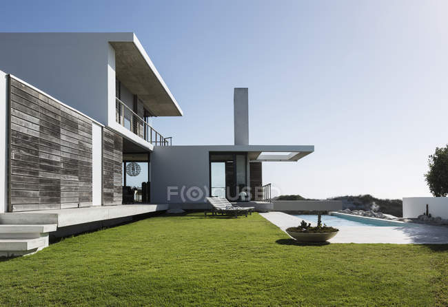 Lawn and lap pool outside modern house — Stock Photo