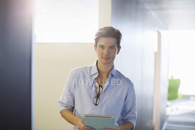 Retrato de homem de negócios sorridente no corredor no escritório moderno — Fotografia de Stock