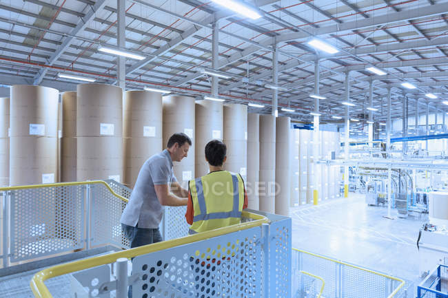Рабочие разговаривают на платформе над заводом — стоковое фото
