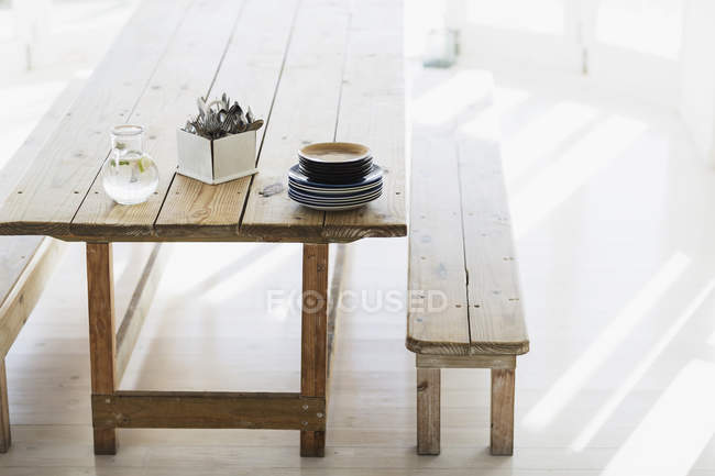 Plates and silverware stacked on wooden table — Stock Photo