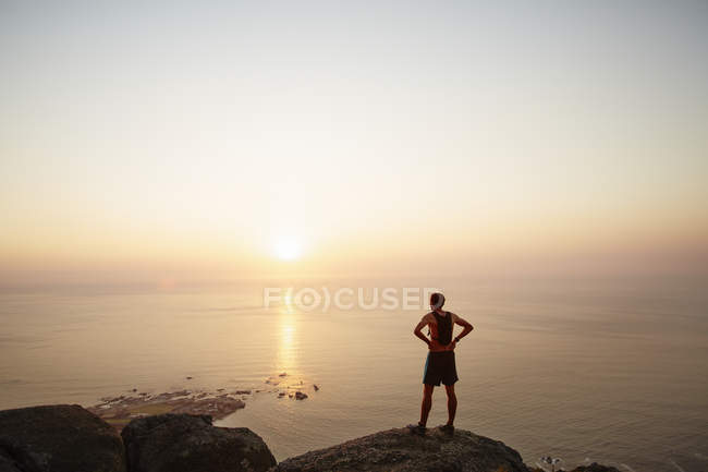 Male runner on rocks looking at sunset ocean view — Stockfoto