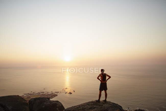 Coureur masculin sur les rochers regardant coucher de soleil vue sur l'océan — Photo de stock