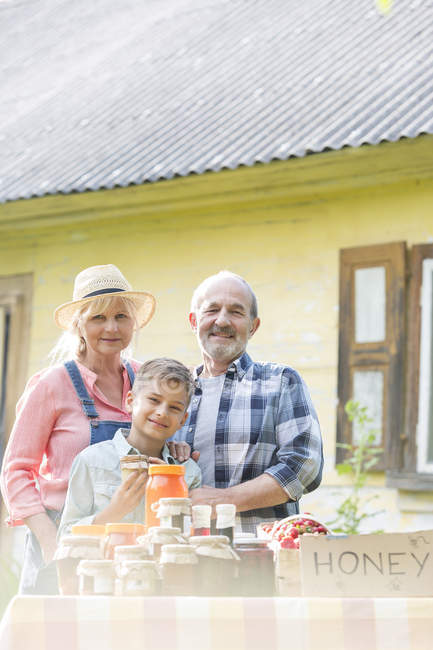 Portrait proud grandparents and grandson selling honey at farmers market stall — Stock Photo