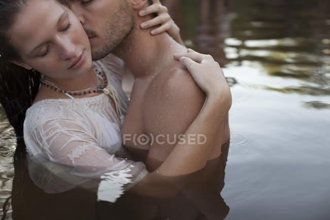 Чувственная пара целуется в озере — стоковое фото