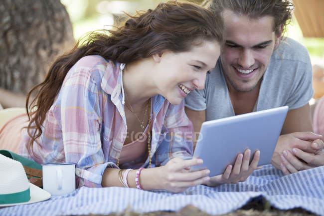 Couple using digital tablet on blanket outdoors — Stock Photo