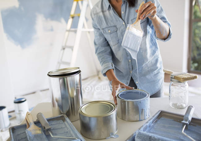Woman holding paintbrush with blue paint — Stock Photo