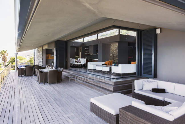 Sofá, mesas e cadeiras na varanda moderna — Fotografia de Stock