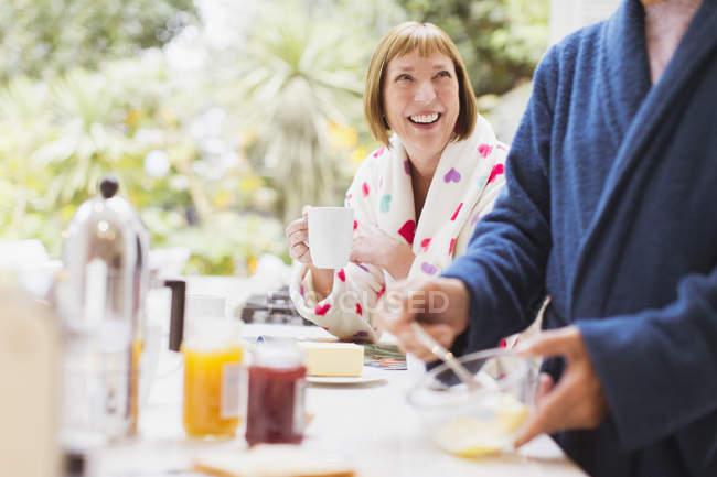 Smiling mature woman drinking coffee in bathrobe at breakfast — Stockfoto