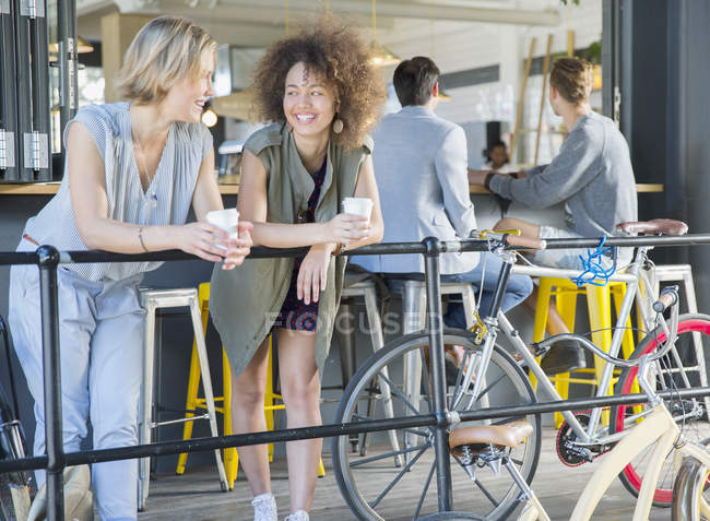 Smiling friends hanging out drinking coffee at cafe patio railing near bicycles — Stock Photo