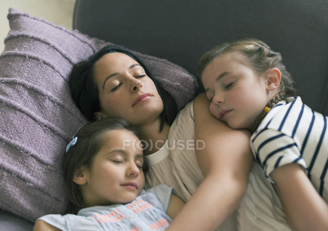 Serene mother and daughters napping on sofa — Stock Photo