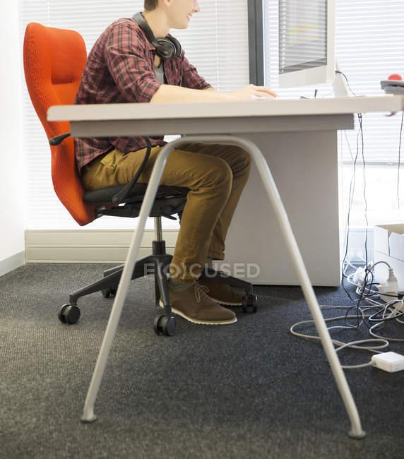 Бизнесмен за компьютером за столом в офисе — стоковое фото