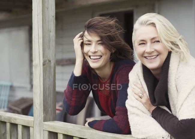 Retrato sorridente mãe e filha no alpendre ventoso — Fotografia de Stock