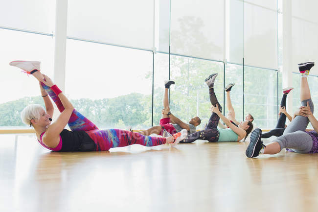 Fitness instructor guiding exercise class stretching legs — Stock Photo